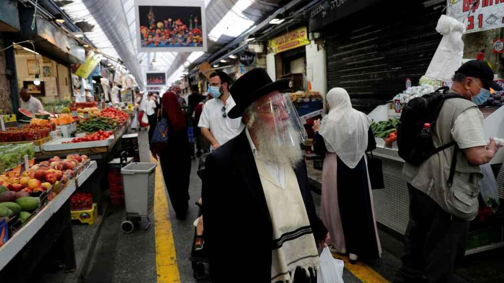 Personas con mascarillas o pantallas protectoras en el principal mercado de Jerusalén.