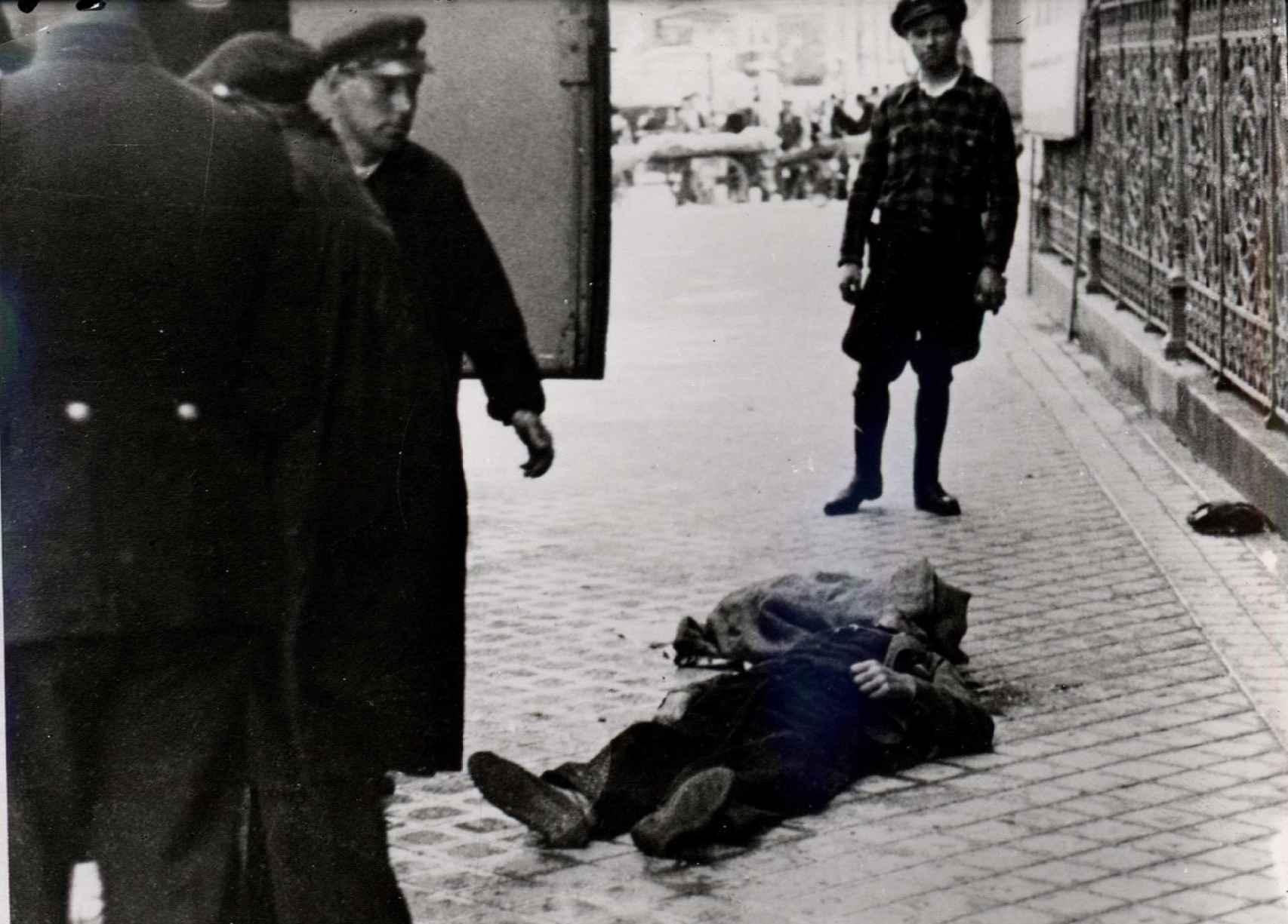 Una persona muerta durante un bombardeo franquista yace delante de la verja del Banco de España.