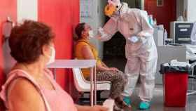 Una enfermera realiza una prueba PCR a una paciente.