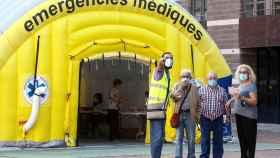 Varias personas acceden a la zona de realización de PCR durante el primer día de cribados masivos de Covid-19 en El Raval de Barcelona