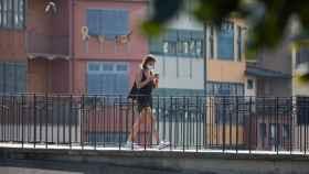 Una joven cruza un puente de Gerona.
