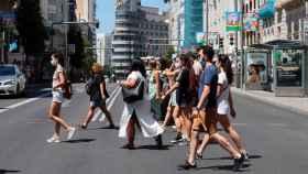 Un grupo de gente cruza la Gran Vía de Madrid con mascarillas.