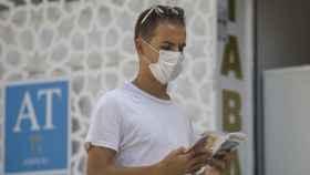 Un turista lee una guía mientras pasea por el casco histórico de Sevilla.