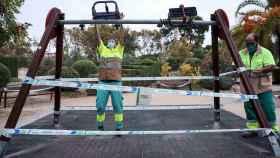 Varios operarios precintan unos columpios en un parque de Valencia este viernes.