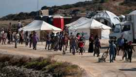 Los refugiados del campo de moria entrando en un campo provisional tras el incendio.