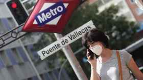 Una mujer pasea al lado del metro de Puente de Vallecas, en Madrid (España).