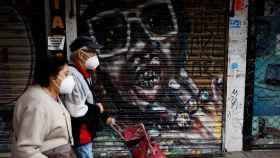 Vecinos de Carabanchel transitan las calles de su barrio este domingo.