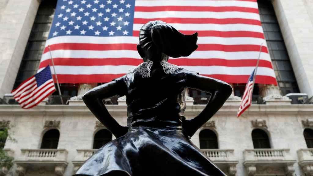 La estatua de 'La Niña' frente a la fachada de Wall Street.