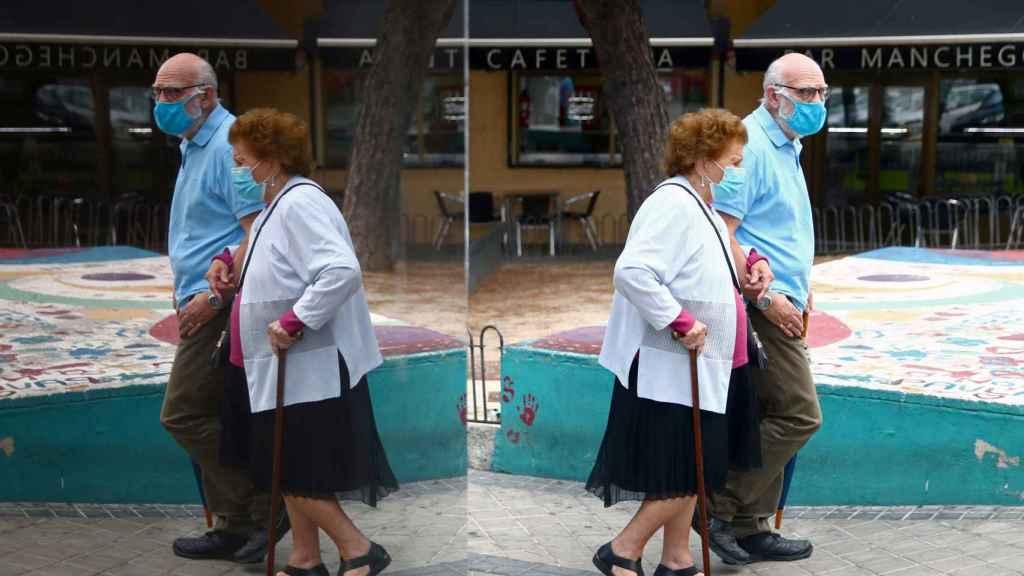 Una pareja de ancianos pasea con mascarilla por las calles de Usera, en Madrid.