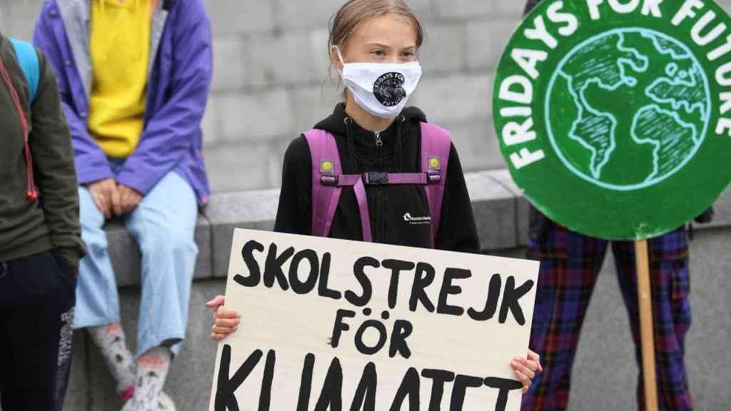 Greta Thunberg sostiene un cartel que dice  Huelga escolar por el clima frente al Parlamento sueco.