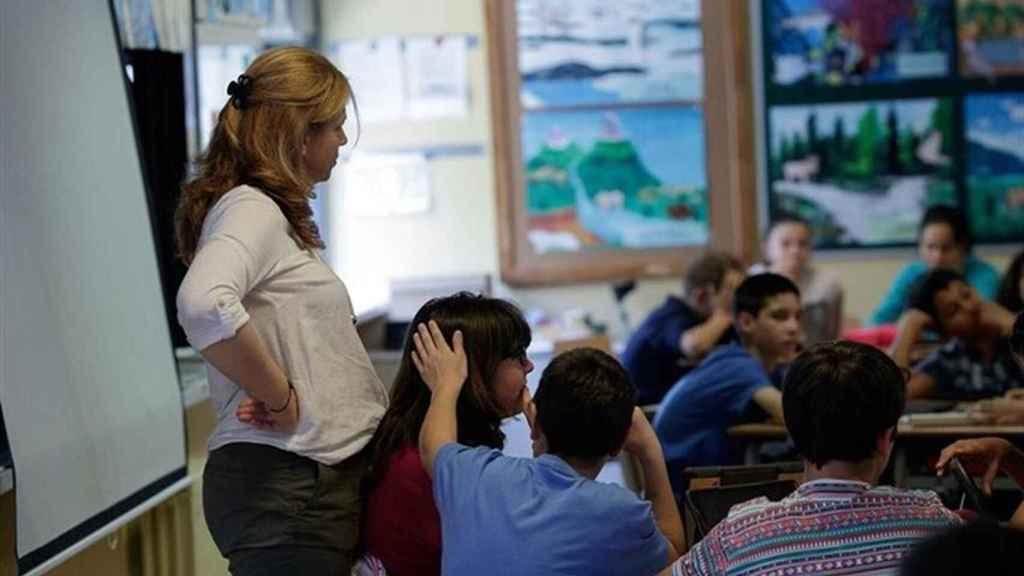 Una profesora da clase en un aula.