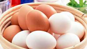 Una cesta de huevos morenos y blancos.