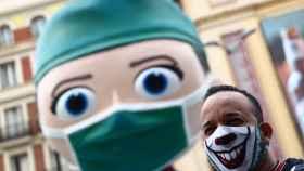 Una persona con una mascarilla decorada junto a la figura del 'súper sanitaria' de Callao. Reuters/Sergio Pérez