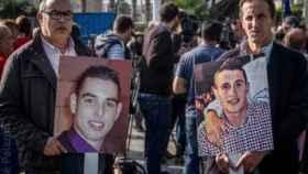Fotos de Abdeslam Ahmed Ali (izqda.) y Mohamed Amin Mohamed Driss, portadas por sus padres en un acto para pedir justicia.