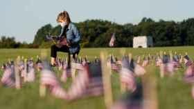 En Washington, una joven coloca banderas por cada una de las más de 200.000 víctimas de la Covid-19 en EEUU.
