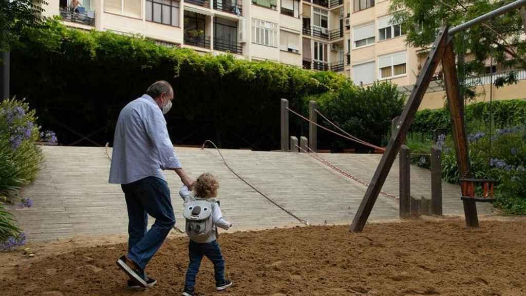 Un abuelo lleva a su nieta al parque en la anterior reapertura en Madrid.