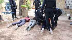 Los tres detenidos, en el suelo y custodiados por la Policía Nacional