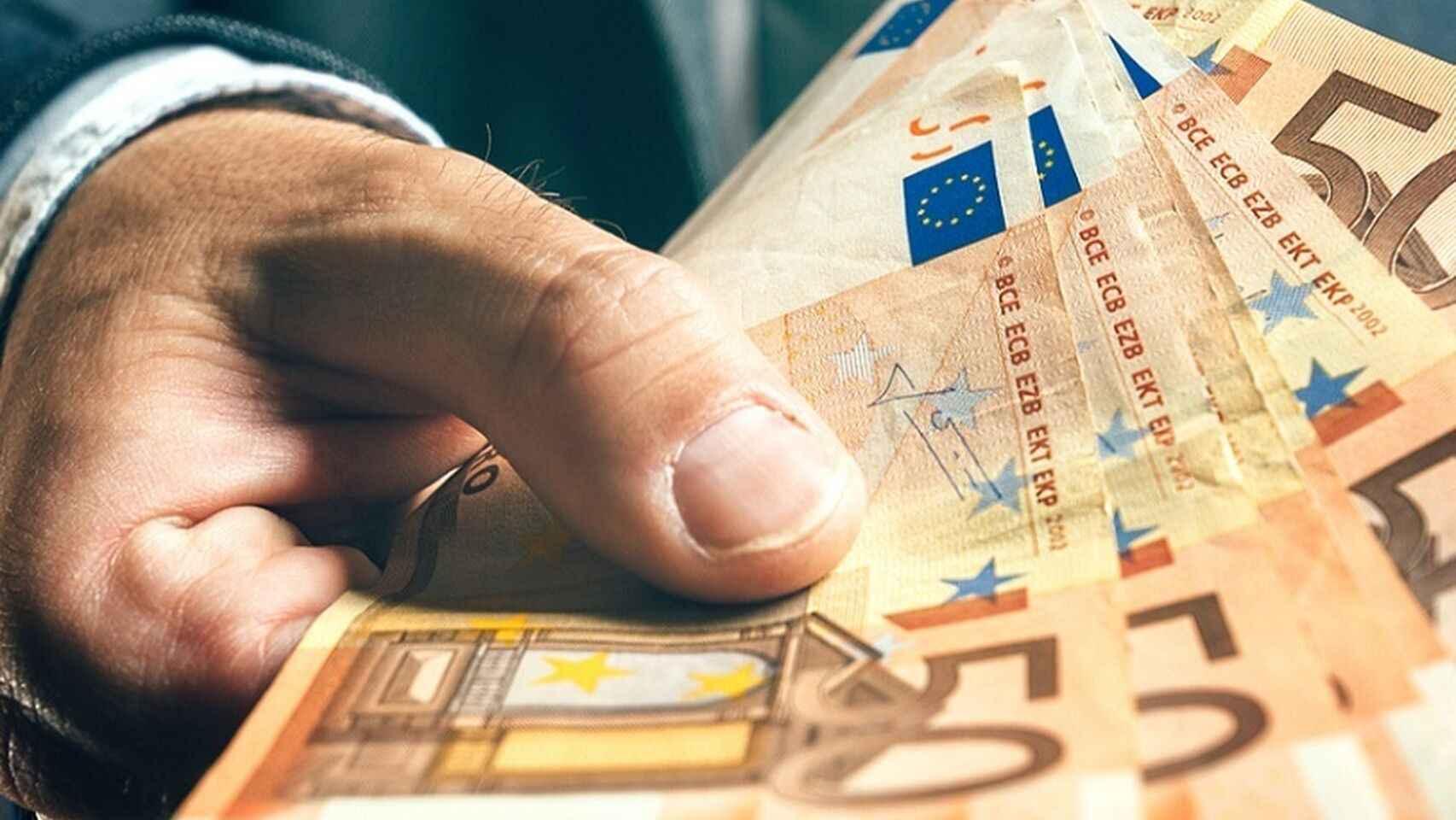 Una mano sostiene billetes de euros.
