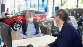 Imagen de un usuario en un concesionario interesándose por un coche nuevo.