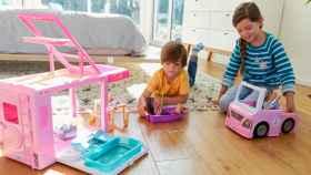 Un niño y una niña jugando con muñecas.