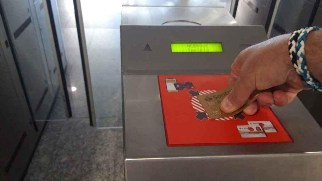 Un usuario paga el trayecto de Cercanías de Renfe con una tarjeta bancaria