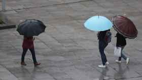 Unos viandantes se protegen de la lluvia traída por la tormenta Álex en Bilbao.