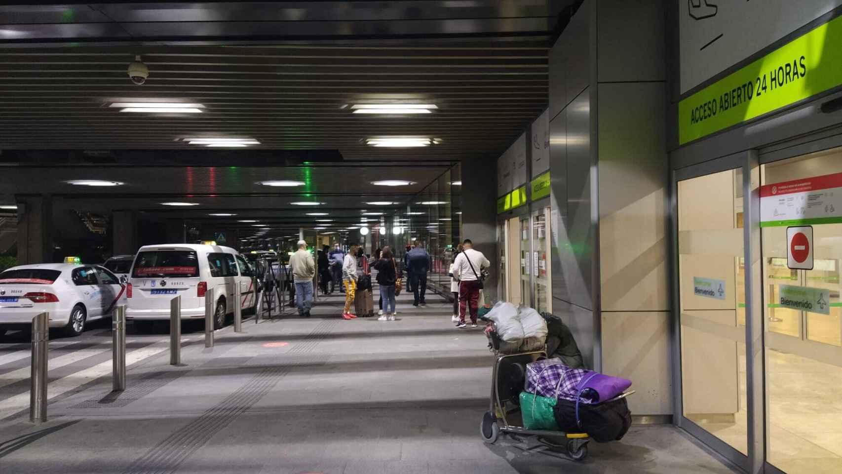 Escasos viajeros esperan en la puerta de la T-1 de Barajas su vuelo.