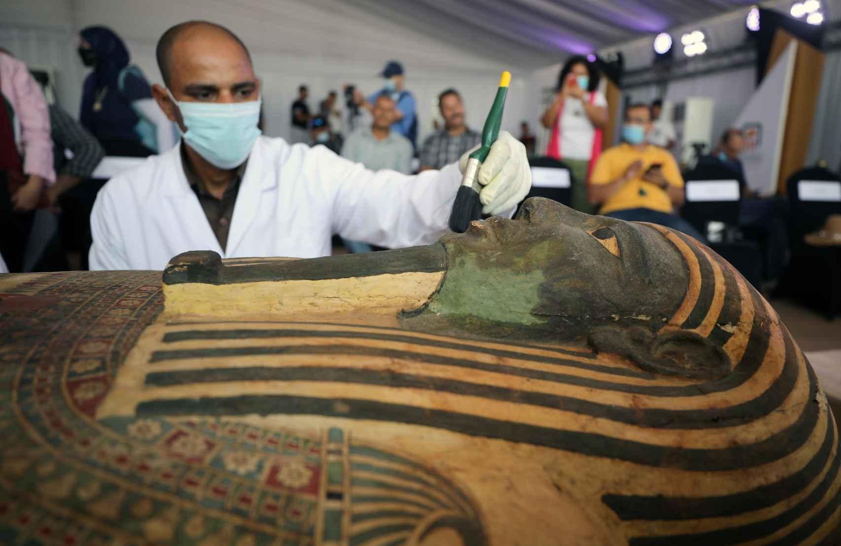 Un restaurador trabajando sobre uno de los sarcófagos hallados.