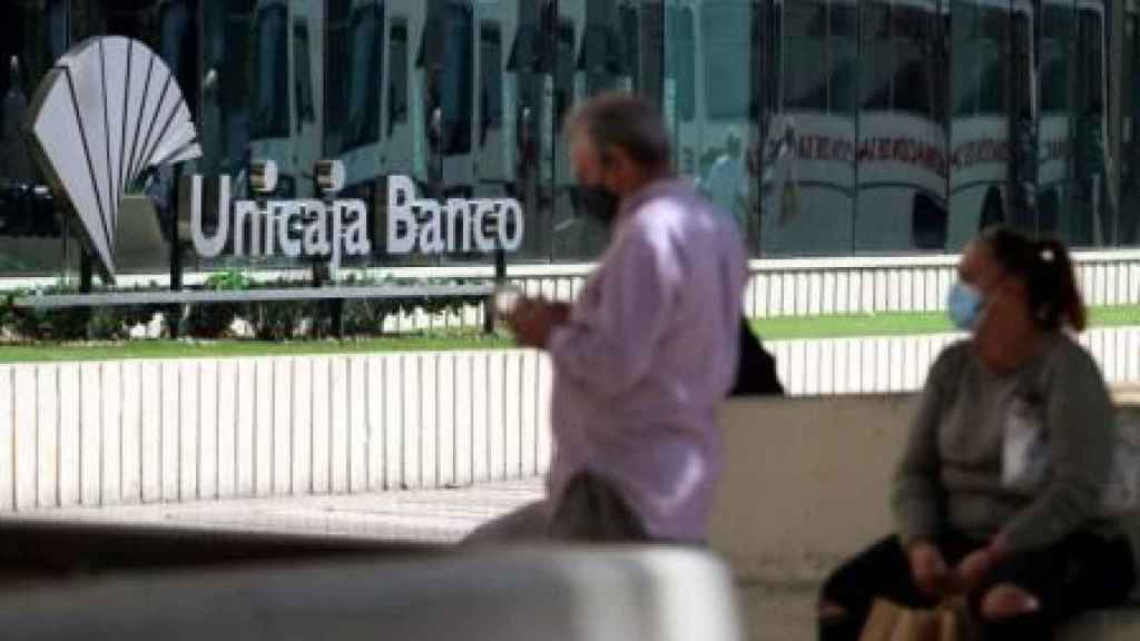 Dos personas frente a la sede de Unicaja en Málaga.