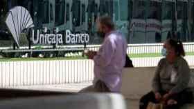 Dos personas frente a la sede de Unicaja Banco en Málaga | EP