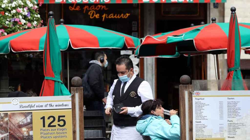 Un camarero con mascarilla trabajando en un restaurante de la Grand Place de Bruselas.