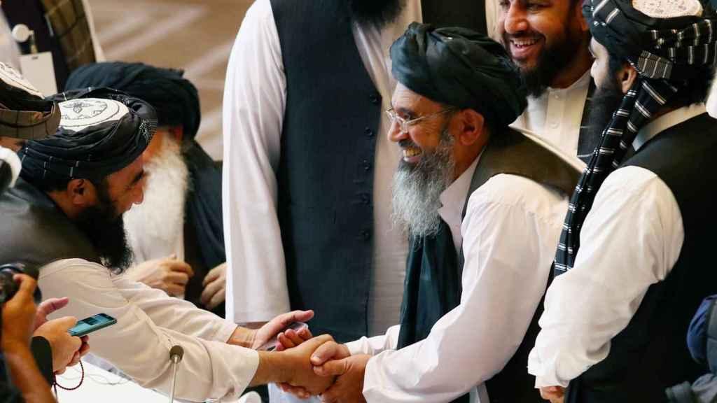 Los delegados talibanes se dan la mano durante las conversaciones.