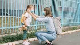 Una madre, agachada, atiende a su hija.