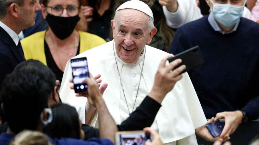 El papa, sin mascarilla, rodeado de fieles que sí la llevan.