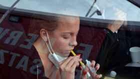 Una joven realiza un test de gárgaras desde su coche para detectar la Covid-19.