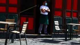 Un camarero, en la puerta de un bar madrileño.