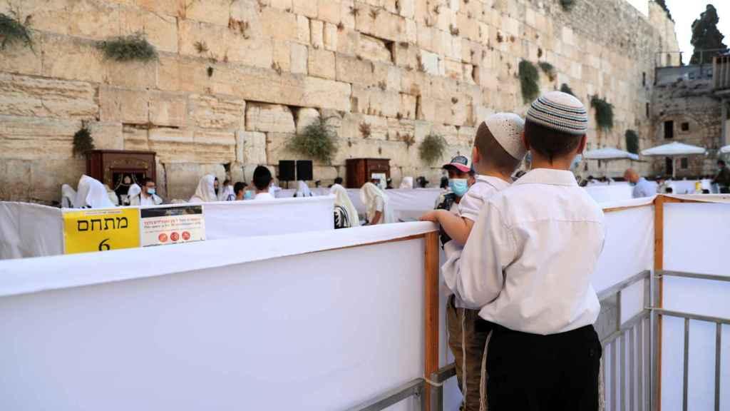 Dos niños miran a los fieles judíos en el Muro de las Lamentaciones.