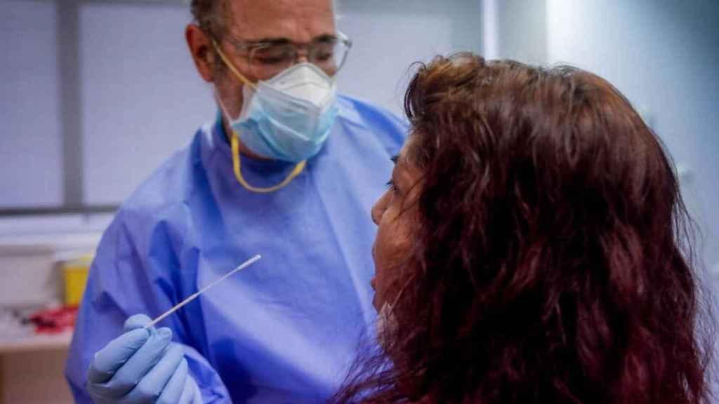 Un sanitario realiza una prueba PCR a una paciente