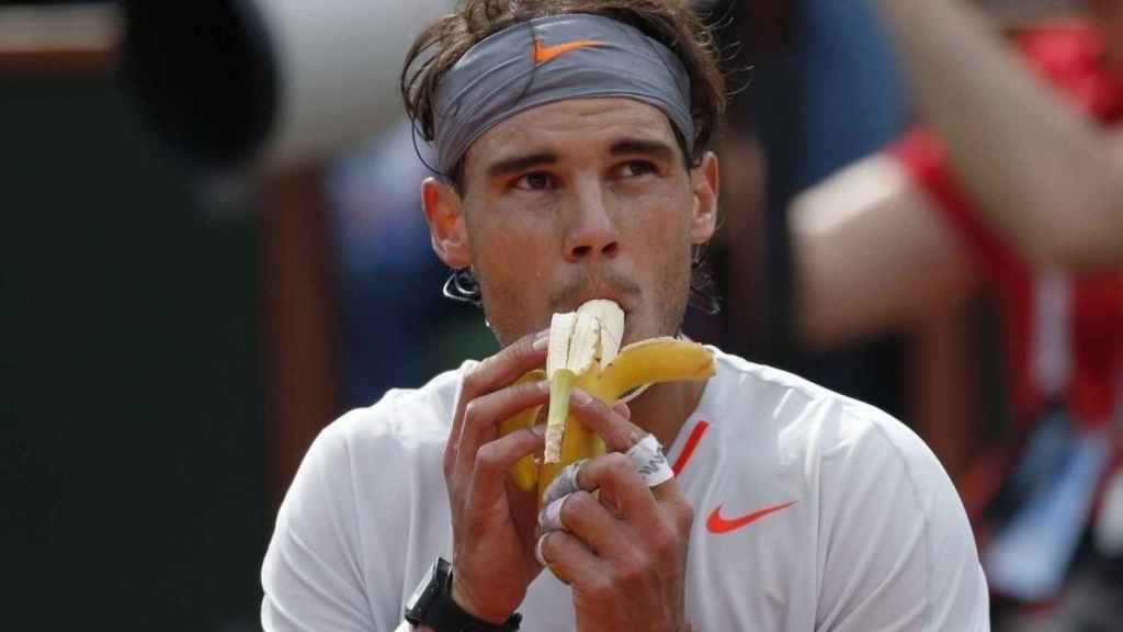 Rafa Nadal dándole un bocado a un plátano durante el descanso de un partido.