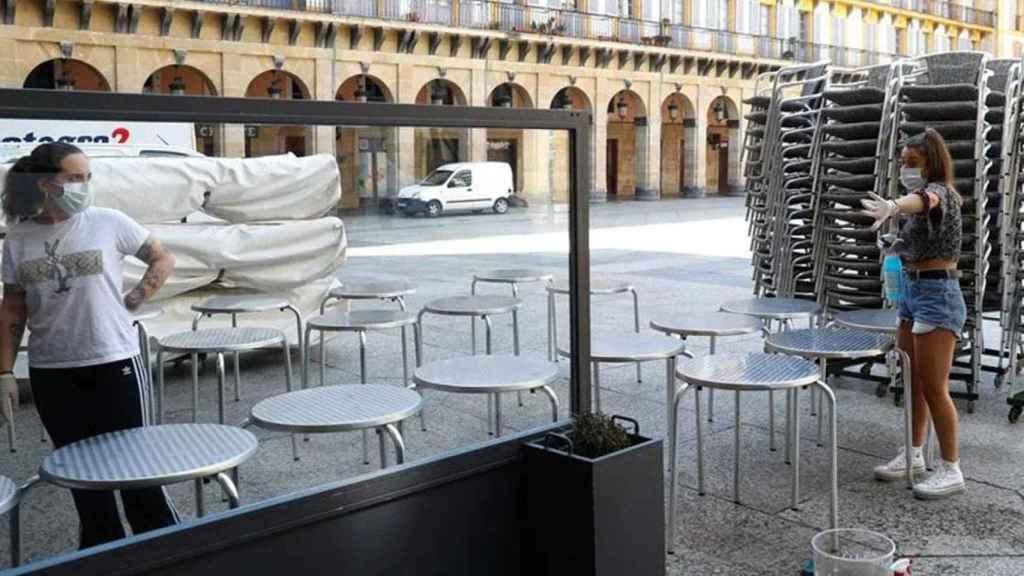 Empleadas de un bar  de Cataluña preparan una terraza.