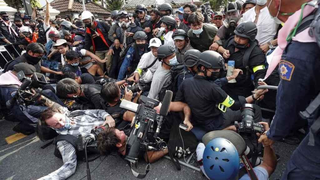 Manifestantes y periodistas caen al suelo durante una manifestación.