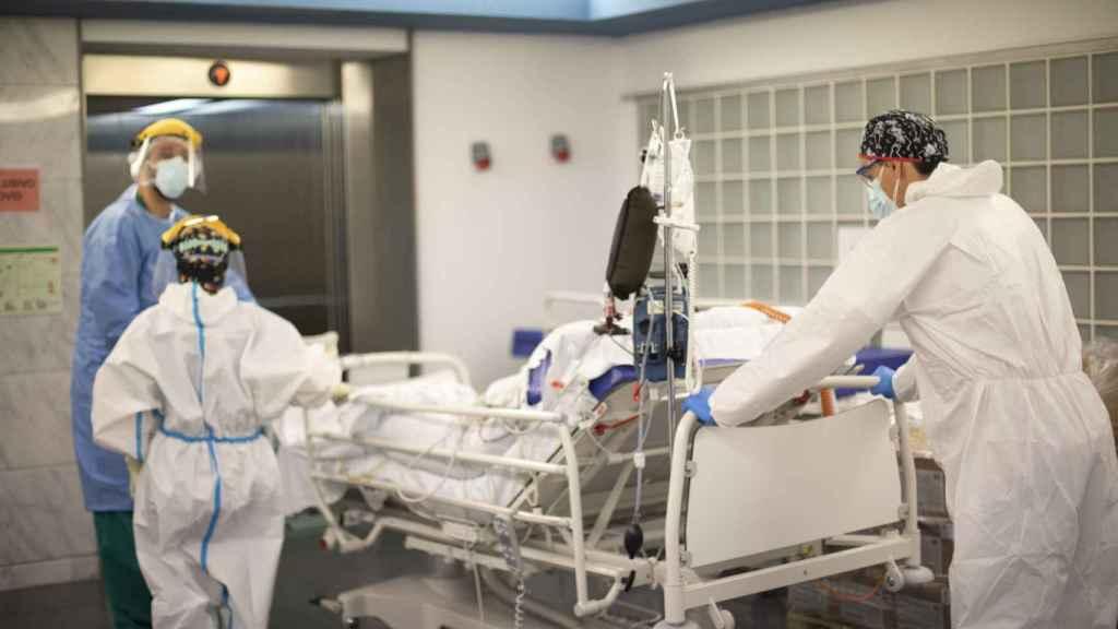 Los sanitarios trasladan a un paciente extubado a la Unidad de Rayos para hacerle un TAC.