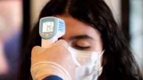 Personal sanitario mide la temperatura corporal de una mujer. EFE/Jeffrey Arguedas
