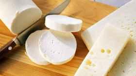 Un par de quesos encima de una tabla de madera.