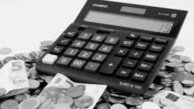 Monedas y billetes junto a una calculadora.