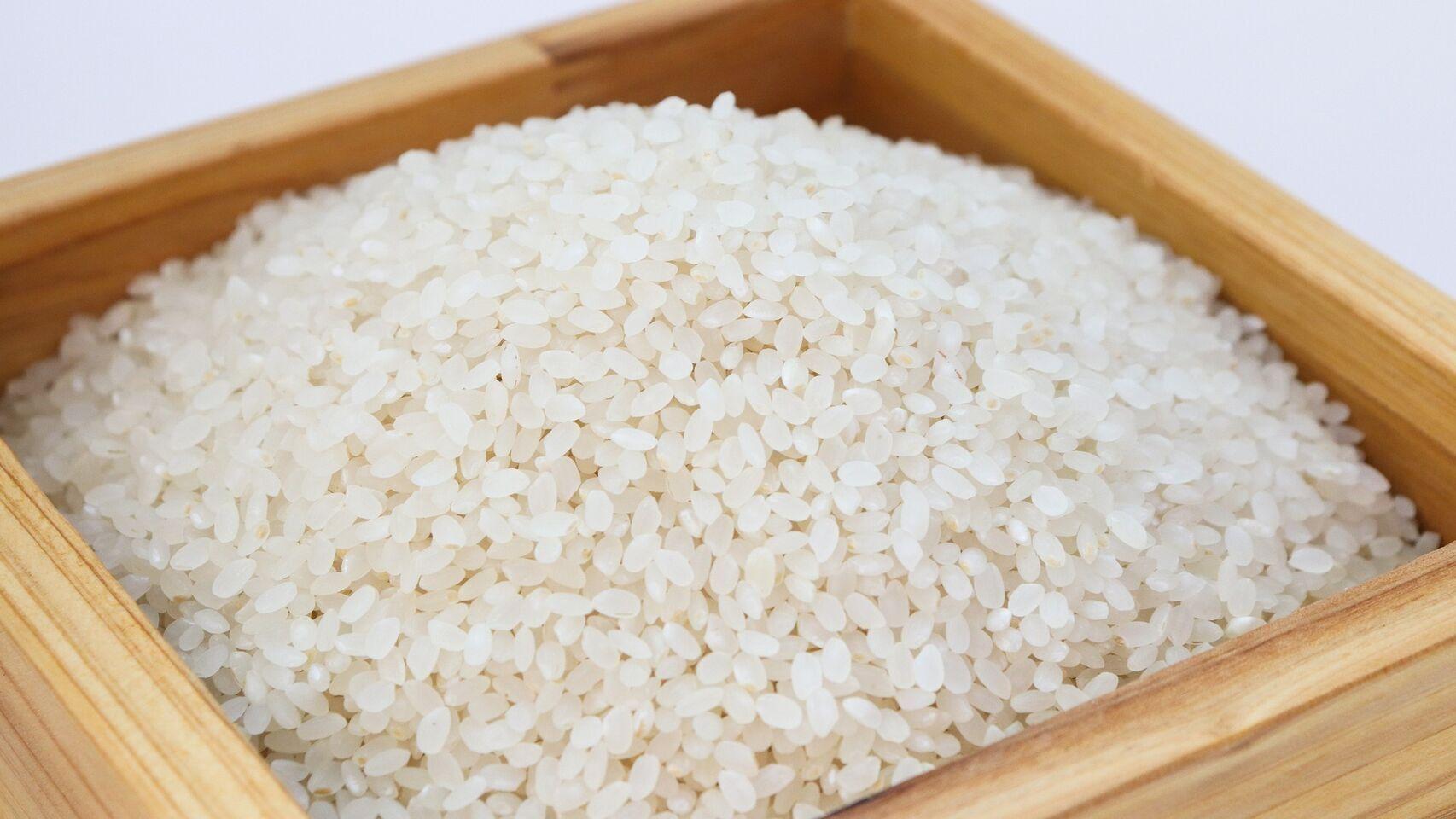 Una caja de madera con arroz crudo.