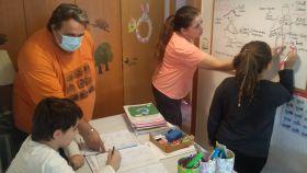 Román, y su mujer, María, dando clase a sus hijos en su casa de Las Torres de Cotillas (Murcia).