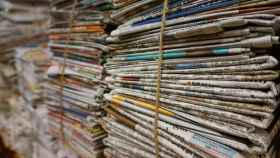 Montones de papel periódico en una planta de reciclaje.
