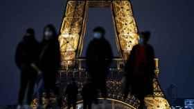 Varios transeúntes portan mascarillas ante la Torre Eiffel en París.
