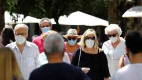 Ciudadanos pasean por una calle de Córdoba con sus mascarillas.